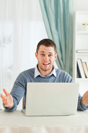 Young businessman having no idea whats wrong with his laptop in his homeoffice photo