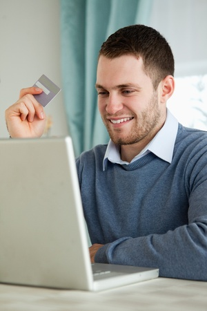 Young man with credit card on his laptop photo