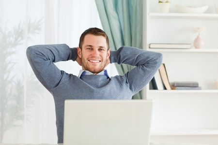 Smiling young businessman leaning back in his homeoffice photo