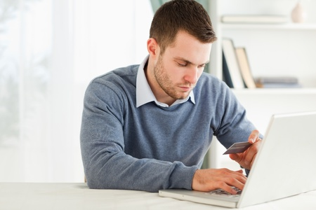 entering information: Young male entering credit card information in his laptop Stock Photo