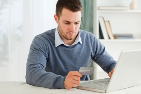 entering information: Young male entering credit card information in his notebook Stock Photo