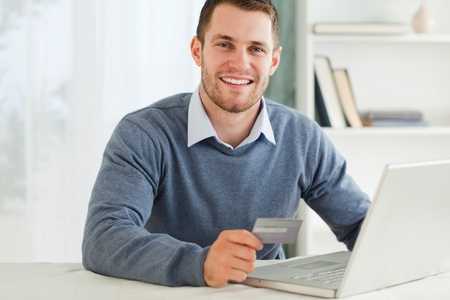 Young male with credit card at his laptop photo