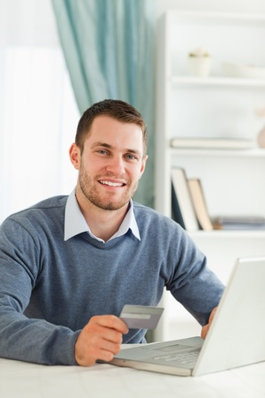Smiling young male with credit card at his notebook photo