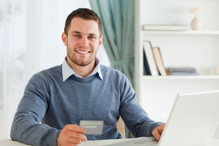 Smiling young male with credit card at his laptop photo