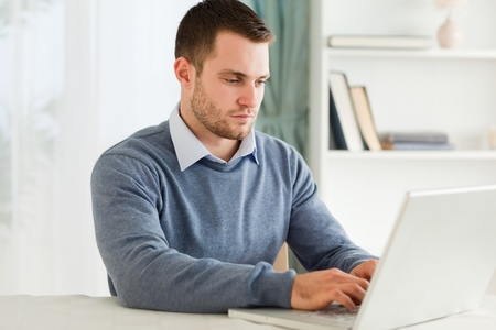 telecommuting: Young man working on his notebook Stock Photo
