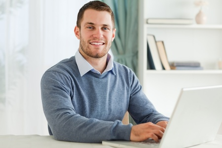 Smiling young businessman with laptop in his homeoffice photo