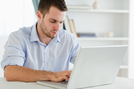 rolled up sleeves: Young businessman with rolled up sleeves in his homeoffice on his laptop