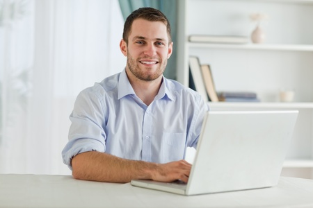 Smiling businessman with rolled up sleeves on his laptop in his homeoffice photo