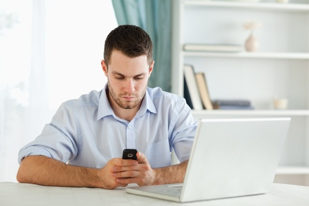 Young businessman texting in his homeoffice photo
