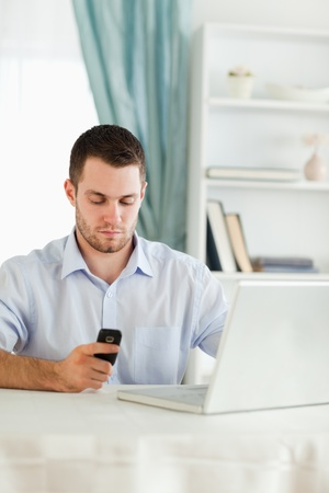 Young businessman texting on his cellphone in his homeoffice photo