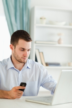 Young businessman holding cellphone while typing photo