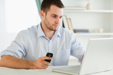 Young businessman typing on his laptop while holding his cellphone photo