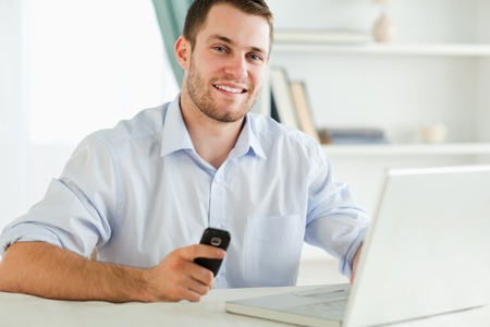 Smiling young businessman holding his cell while typing on his laptop photo