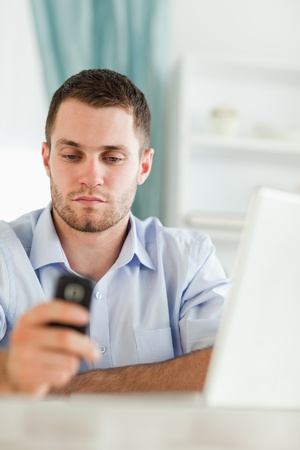 Young businessman texting on his cellphone sitting behind his desk photo