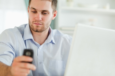 Young businessman with laptop and mobile phone photo