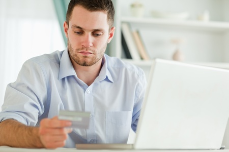 Young businessman with credit card and laptop photo