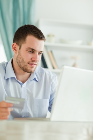 Young businessman with credit card and laptop in his homeoffice photo