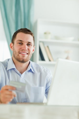 Young businessman with credit card and notebook in his homeoffice photo