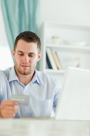 Young businessman with laptop and credit card in his homeoffice photo
