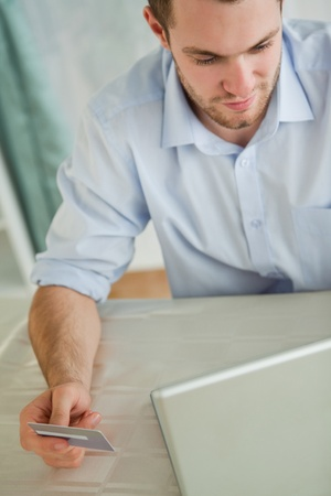 Young businessman with credit card on his laptop Stock Photo - 11632544