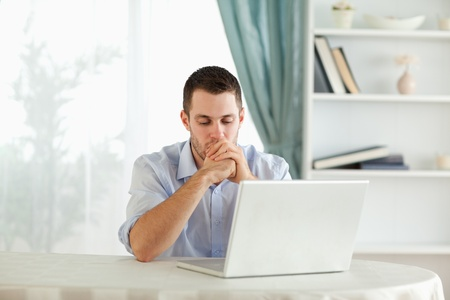 confus: Lecture jeune homme d'affaires sur son ordinateur portable