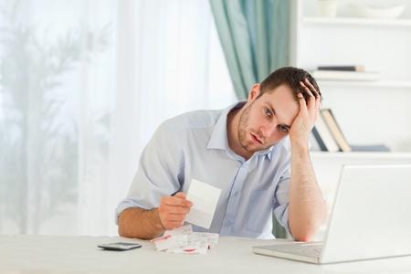 pagando: Joven hombre de negocios preocupado por una factura