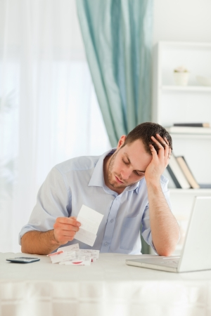 Concerned young businessman looking at an invoice photo