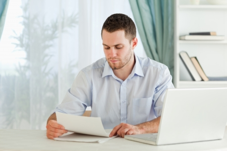 Young businessman reading a letter in his homeoffice photo