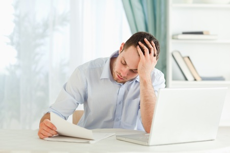 alarming: Young businessman reading an alarming letter