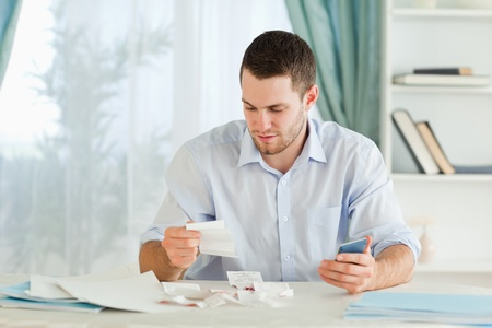 Young businessman with calculator checking bills photo