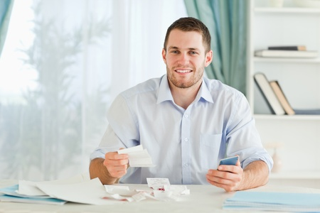 Young businessman with pocket calculator checking bills photo