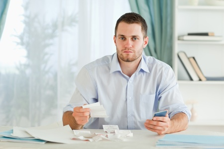 Young businessman with calculator checking invoices photo