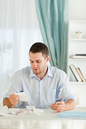 Young businessman with hand calculator checking bills photo