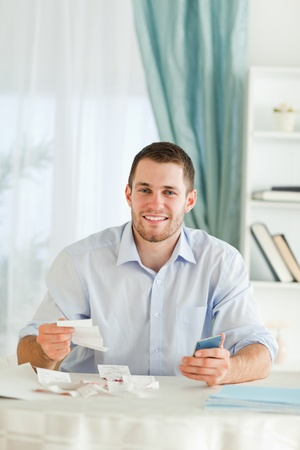 Young businessman with hand calculator checking invoices photo
