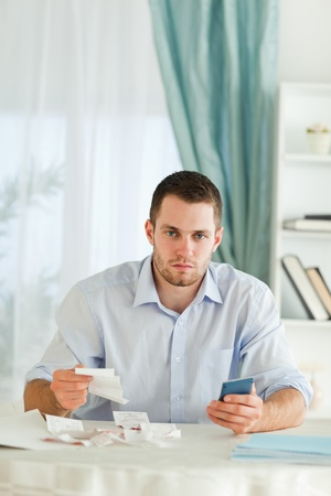 Serious looking young businessman doing accounting photo