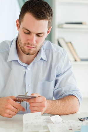 Young businessman cutting his credit card photo