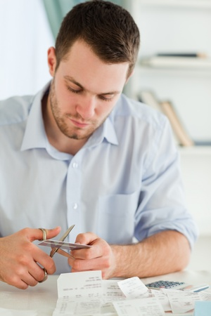 Young businessman cutting his credit card into pieces photo