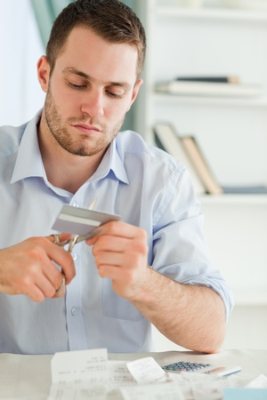 Young businessman using scissor to destroy his credit card photo
