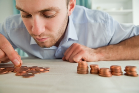 money problems: Young businessman counting coins