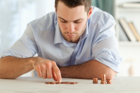 Young businessman counting his small coins photo