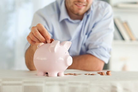 Small change being put into piggy bank photo