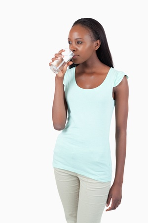 Young female having a sip of water against a white background Stock Photo - 11637102