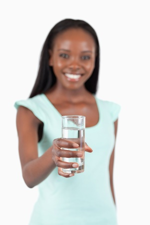offered: Refreshing glass of water offered by young woman against a white background