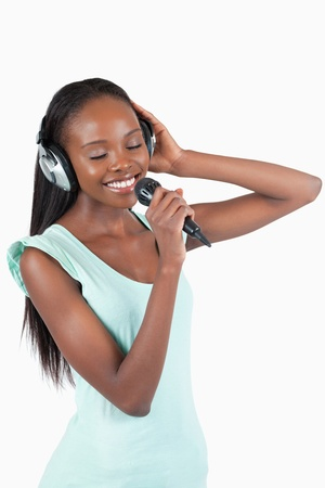 kareoke: Smiling young woman singing against a white background Stock Photo