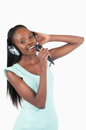 kareoke: Happy smiling young woman singing against a white background