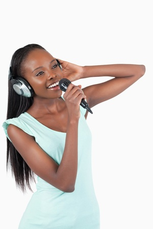 kareoke: Young woman with headphones singing against a white background