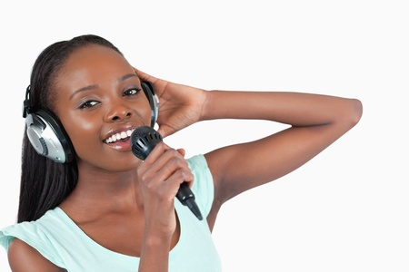 kareoke: Woman with headphones on singing against a white background Stock Photo