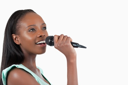 kareoke: Woman with microphone singing against a white background