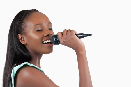 kareoke: Smiling young woman singing into a microphone against a white background Stock Photo