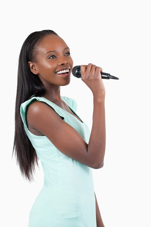 kareoke: Happy smiling young female singer against a white background